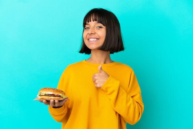 Giovane donna castana che tiene un hamburger sopra fondo isolato che dà un gesto di pollice in alto