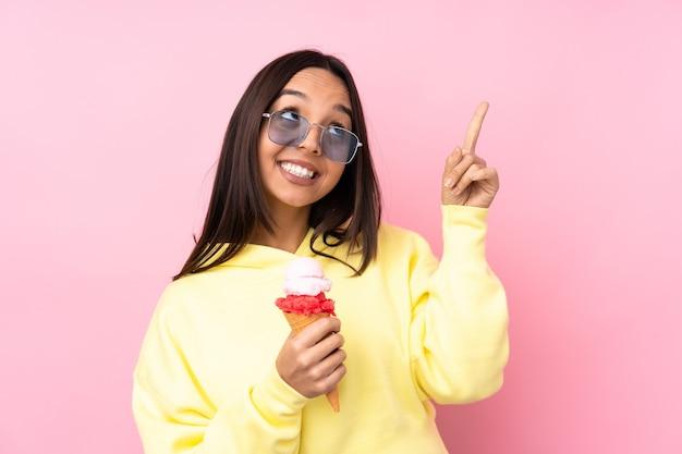 Giovane donna castana che tiene un gelato della cornetta isolato