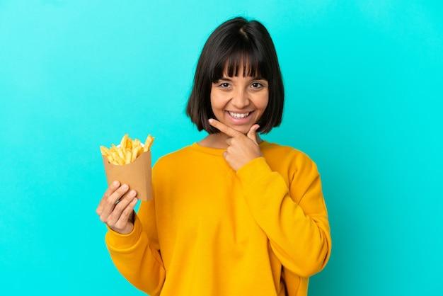 Giovane donna castana che tiene patatine fritte su sfondo blu isolato felice e sorridente