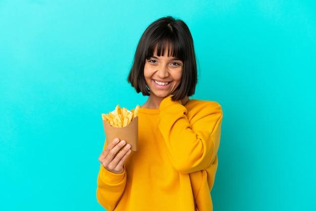 Giovane donna castana che tiene patatine fritte su sfondo blu isolato ridendo Foto Premium