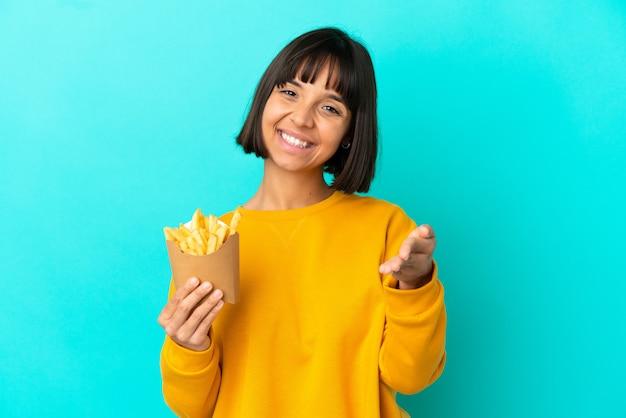 Giovane donna bruna che tiene patatine fritte su sfondo blu isolato che stringe la mano per chiudere un buon affare