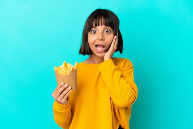 Giovane donna castana che tiene patatine fritte su sfondo blu isolato con espressione facciale sorpresa e scioccata