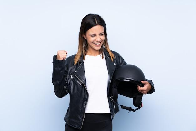 Giovane donna castana che tiene un casco del motociclo sopra la parete blu isolata che celebra una vittoria