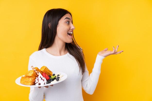 La giovane donna castana che tiene le cialde sopra la parete isolata con espressione facciale di sorpresa