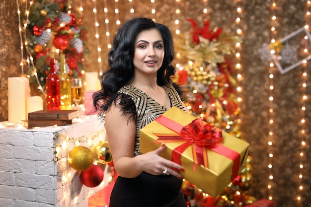 Giovane donna bruna tiene un regalo in una scatola gialla per natale.
