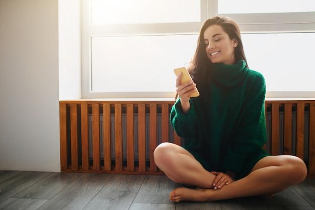 La giovane donna castana sta sedendosi su un davanzale di legno vicino alla finestra