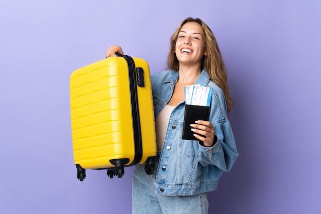 Giovane donna bruna su sfondo blu isolato in possesso di una valigetta vintage