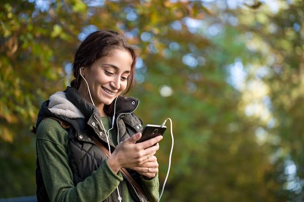 Giovane donna castana che ascolta la musica nel parco di autunno.