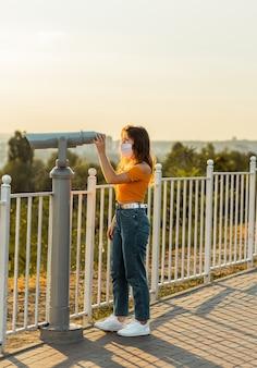 Giovane donna castana guarda attraverso il binocolo nel parco pubblico mentre indossa una mascherina chirurgica.
