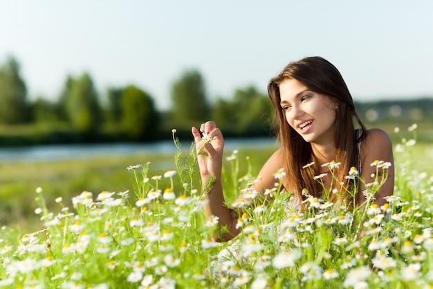 Giovane donna castana che si trova sull'erba e che sorride il giorno di estate con la natura verde e fiume al fondo