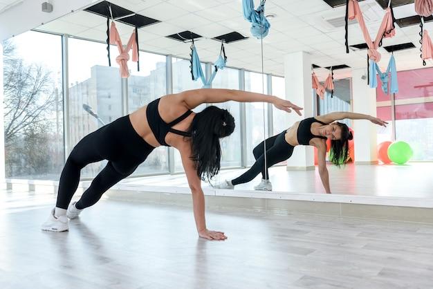 Giovane donna castana facendo esercizi in palestra