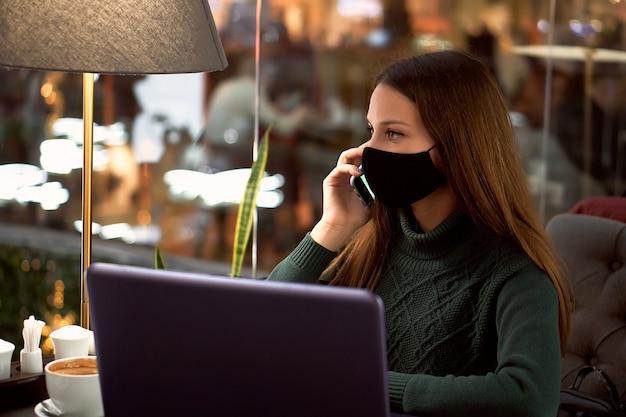 Giovane donna castana nella mascherina medica nella caffetteria con il computer portatile