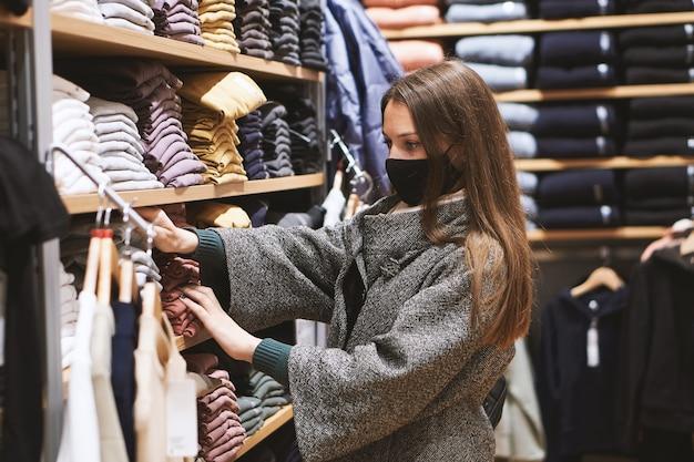La giovane donna castana in mascherina medica sceglie i vestiti nel negozio e fa acquisti