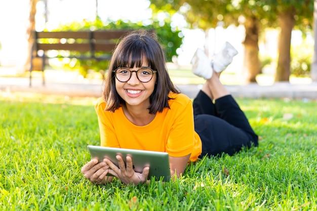 Giovane donna castana all'aperto che tiene un tablet