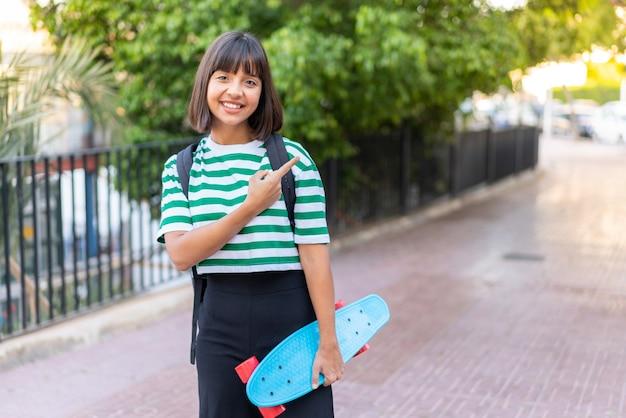 Giovane donna bruna all'aperto con un pattino e indicando il lato