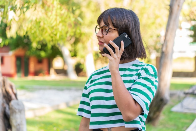Giovane donna castana nel parco che tiene una conversazione con il telefono cellulare con qualcuno