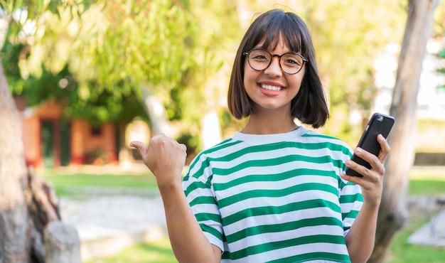 Giovane donna castana nel parco usando il telefono cellulare e indicando il laterale