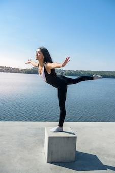 Giovane donna castana a praticare yoga la mattina presto prima dell'orario di lavoro. concetto di benessere e stile di vita sano