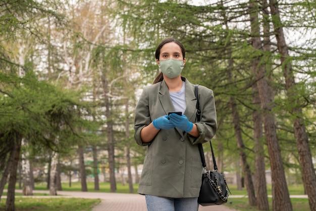 Giovane donna castana in guanti protettivi e maschera che ti guarda mentre si utilizza il telefono cellulare