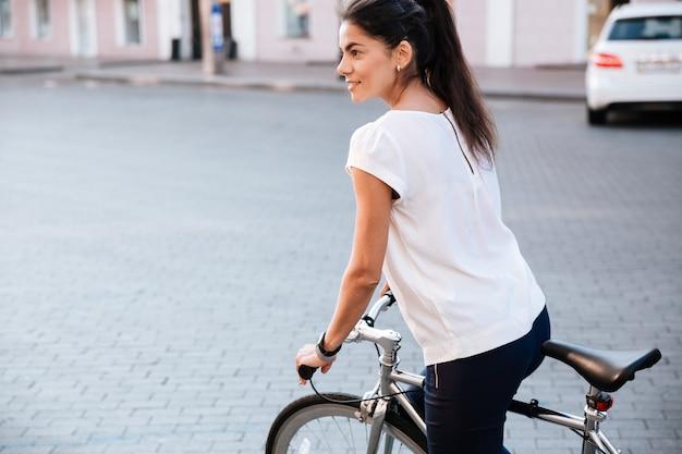 Giovane donna castana che guida sulla bicicletta nella via della città