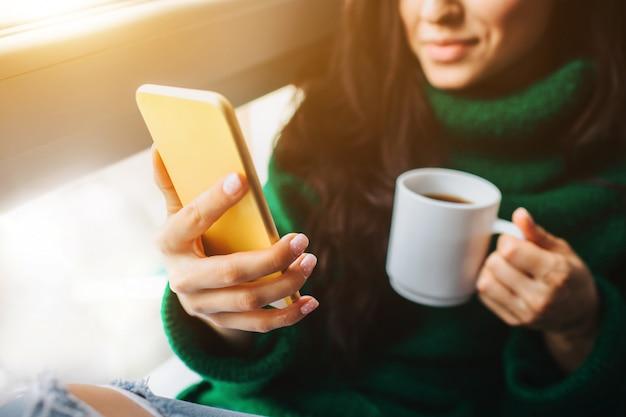Una giovane donna bruna si siede su un davanzale e in possesso di uno smartphone e una tazza di tè