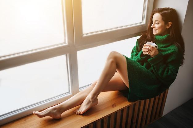 Una giovane donna bruna si siede su un davanzale e tiene in mano una tazza di tè