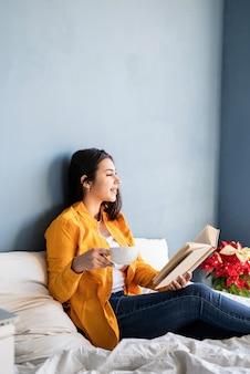Giovane donna bruna seduta nel letto con mangiare croissant e leggere un libro