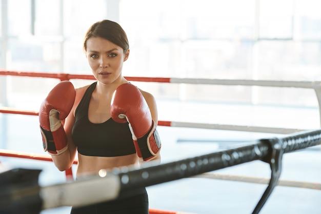 Giovane donna castana in abbigliamento sportivo e guantoni da boxe in piedi all'interno del ring pronto a combattere