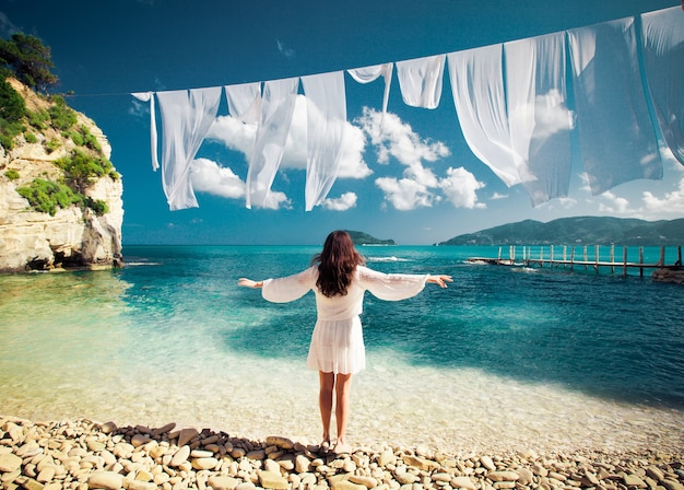 Giovane donna castana in abito bianco estivo in piedi sulla spiaggia e guardando il mare. ragazza caucasica che si rilassa e si gode la pace in vacanza. isola della grecia.