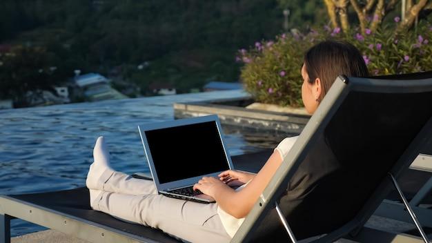 La giovane donna castana scrive sul computer portatile che riposa nella sedia pieghevole vicino alla piscina dell'hotel contro la vista laterale del cespuglio fiorito