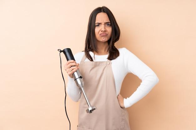 Giovane donna del brunette che per mezzo del miscelatore della mano arrabbiato
