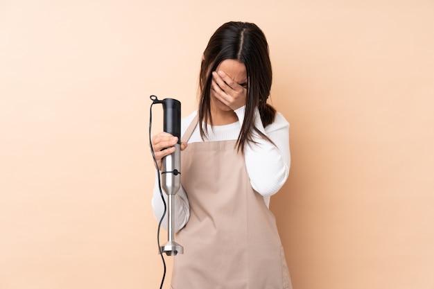 Giovane donna del brunette che per mezzo del miscelatore della mano con l'espressione stanca e ammalata