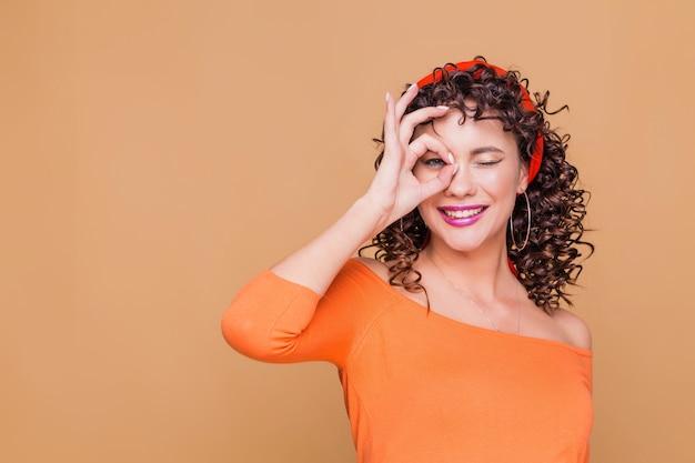 Giovane donna castana che indossa bandana e camicetta arancione facendo il gesto giusto con la mano sorridente