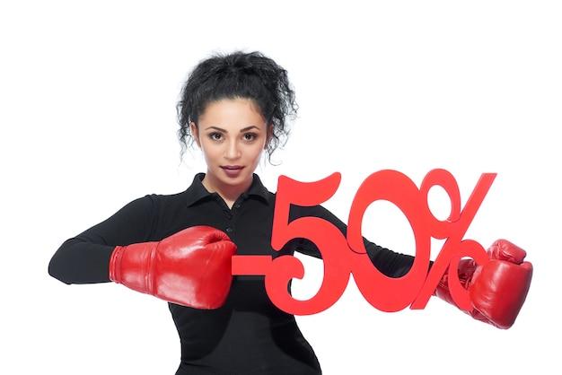 Giovane donna bruna che indossa guantoni da boxe punzonatura -50 sconto segno vendita vendita offerta prezzi shopping consumismo acquisto acquisto concetto.