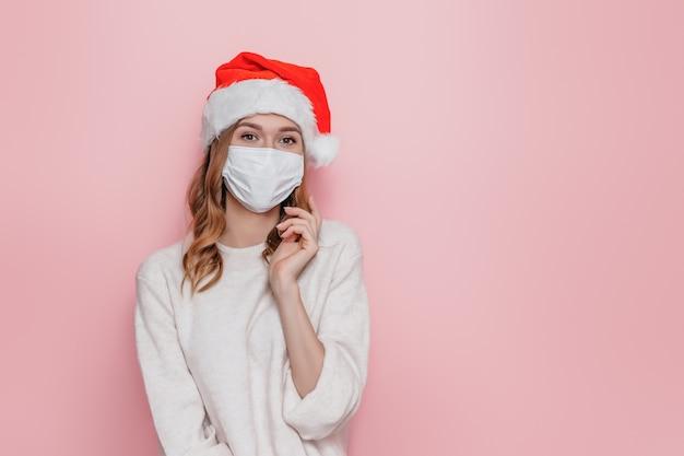 Giovane donna bruna che indossa una maschera medica protettiva un cappello di natale e un maglione bianco in posa su una parete rosa