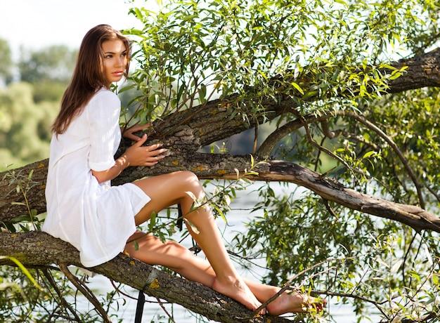 Giovane donna castana in vestito bianco che si siede sul tronco di albero sopra l'acqua il giorno di estate con la natura verde al fondo