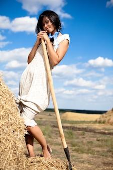Giovane donna bruna in abito bianco in piedi con forcone di fieno in mano in campo in una limpida giornata estiva