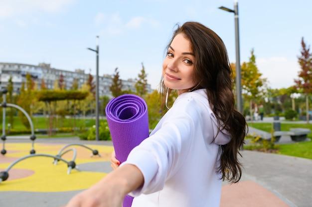 Giovane donna bruna in felpa con cappuccio bianca, con in mano un tappetino sportivo viola sullo sfondo del parco cittadino, torna indietro, tienimi la mano, seguimi idea di tendenza