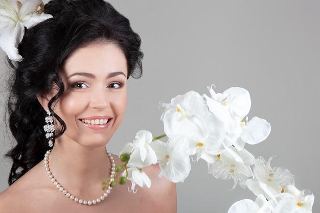 Giovane donna castana con una bella acconciatura, collana di perle e orecchini circondati da sorridere