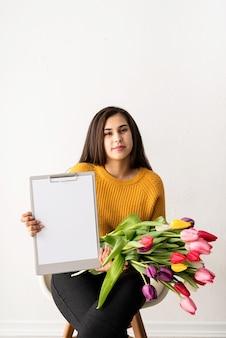 Giovane donna castana con bouquet di tulipani rosa freschi e appunti in bianco