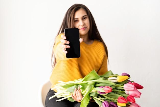 Giovane donna castana con bouquet di tulipani rosa freschi e telefono cellulare in bianco