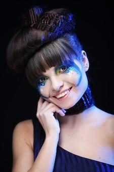 Giovane donna castana con trucco luminoso sull'azzurro
