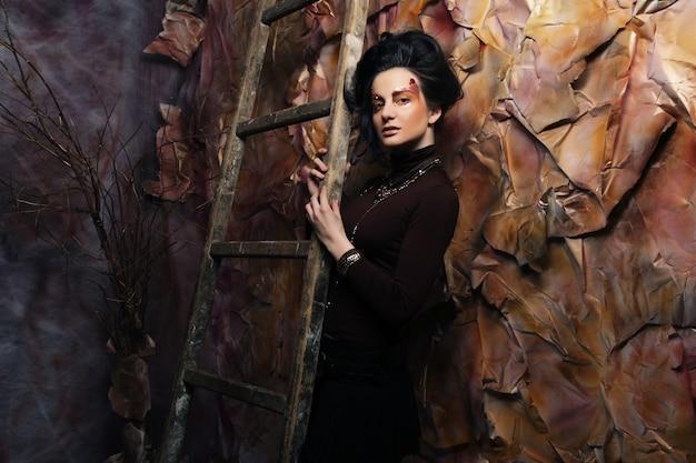 Giovane donna castana con trucco luminoso vicino alle scale