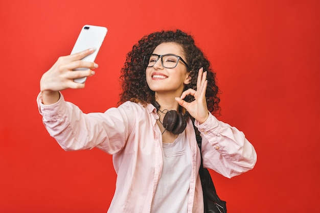 Giovane donna castana con capelli ricci che prendono selfie