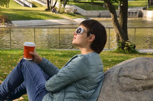 Giovane donna bruna con i capelli corti in un profilo si siede sulla riva dello stagno con una tazza di caffè