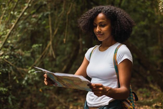 Giovane donna castana con la camicia bianca che tiene e che esamina la mappa di carta