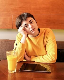 Giovane donna castana in felpa con cappuccio gialla al tavolo con un bicchiere di frullato di mango e tablet. la donna ha appoggiato la testa sulla mano
