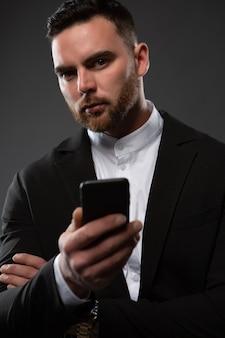 Un giovane uomo d'affari brutale scrive un messaggio su uno smartphone