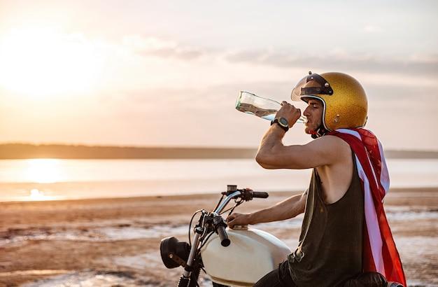 Giovane uomo brutale in casco d'oro e mantello bandiera americana bere e seduto sulla sua motocicletta