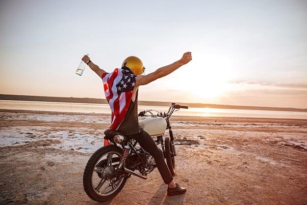 Giovane uomo brutale in casco d'oro e mantello bandiera americana seduto sulla sua moto con le mani in aria